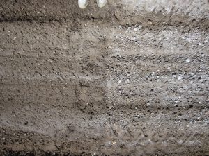 The image shows a soil profile. On the left, the side that has been twice tilled, lime is far better mixed mixed with the soil. On the left (same soil profile - once tilled) lime clumps are visible throughout the profile, demonstrating that tilling twice more thoroughly incorporates the lime.