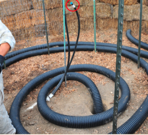 Photo 2. Internal features of the compost water heater: Aeration tubing (100' x 4'' diameter) is placed at the base of the compost water heater with one end inserted into a 2' hole (foreground) and the other end terminating at the hay bale exterior (not shown). Metal conduit marks the center of the pile; the hot water line is attached to it with a zip-tie. The cold water return line is pictured here with a blue cap and white tape (in the red circle); this line will be attached to the heating coil system (see following figure). Metal fence posts are driven into the ground to provide a structure for the fencing and heat coil system that will be attached to it with zip-ties (see subsequent figures).